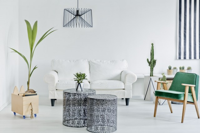 a stark white room with bold furniture of a couch, big ceiling light, striped curtains and fresh plants