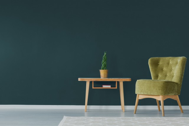 a bright green chair and side table infront of a big bold wall painted with forest green paint