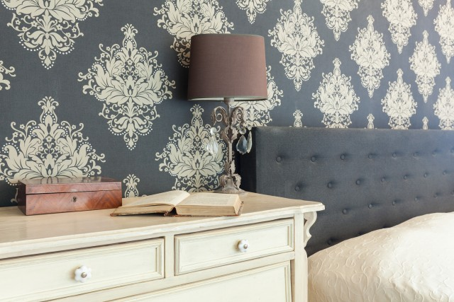 a fabric headboard and antique dresser in front of a bold victorian patterned wallpaper