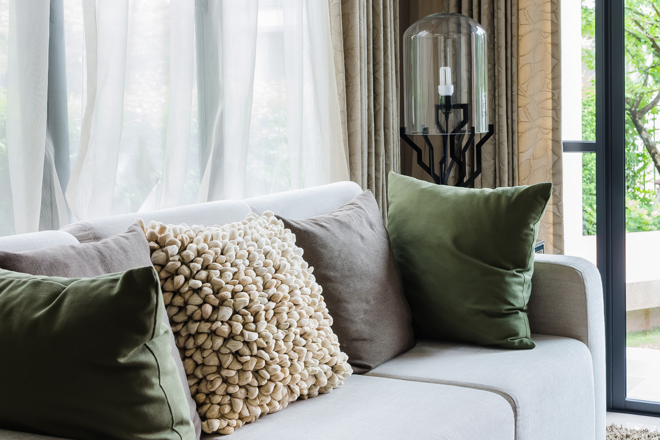 a couch covered in throw pillows in front of a window with soft and breezy curtains