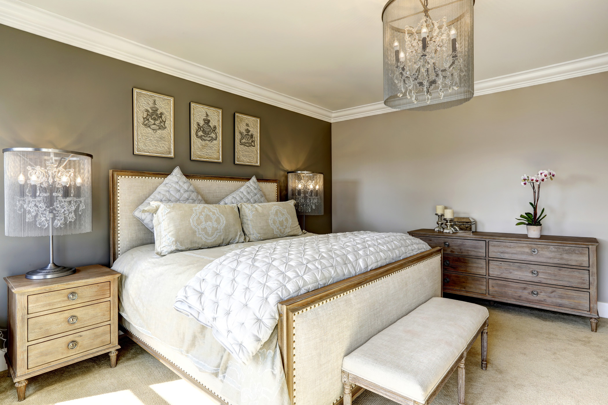 a modern decorated bedroom with a painted beige accent wall decorated with a chandelier, flowers and artwork