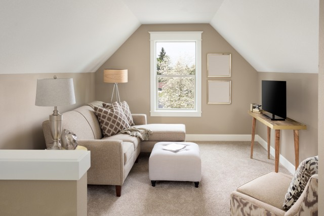 a soft beige painted living room with a bright window, couch and automan