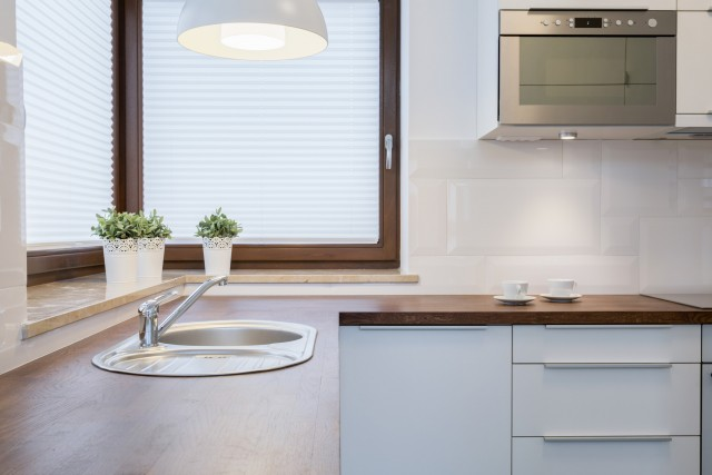 a kitchen corner with bright lights and a roller shaded window covering