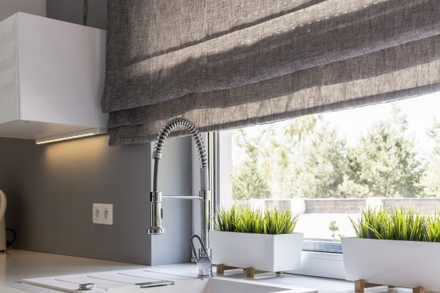 a modern kitchen sink overlooking the bright lit window covered with beautiful roller shades
