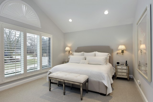 a light grey bedroom with large floor to ceiling windows covered with beautiful shutters