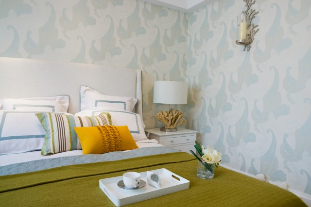 a bright decorated bed covered with throw pillows and a breakfast tray by beautiful blue wave wallpaper