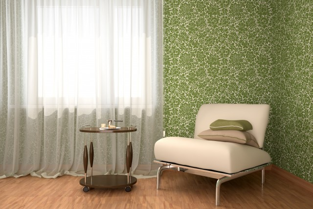 a simple accent chair in front of a green floral wallpaper and bright window
