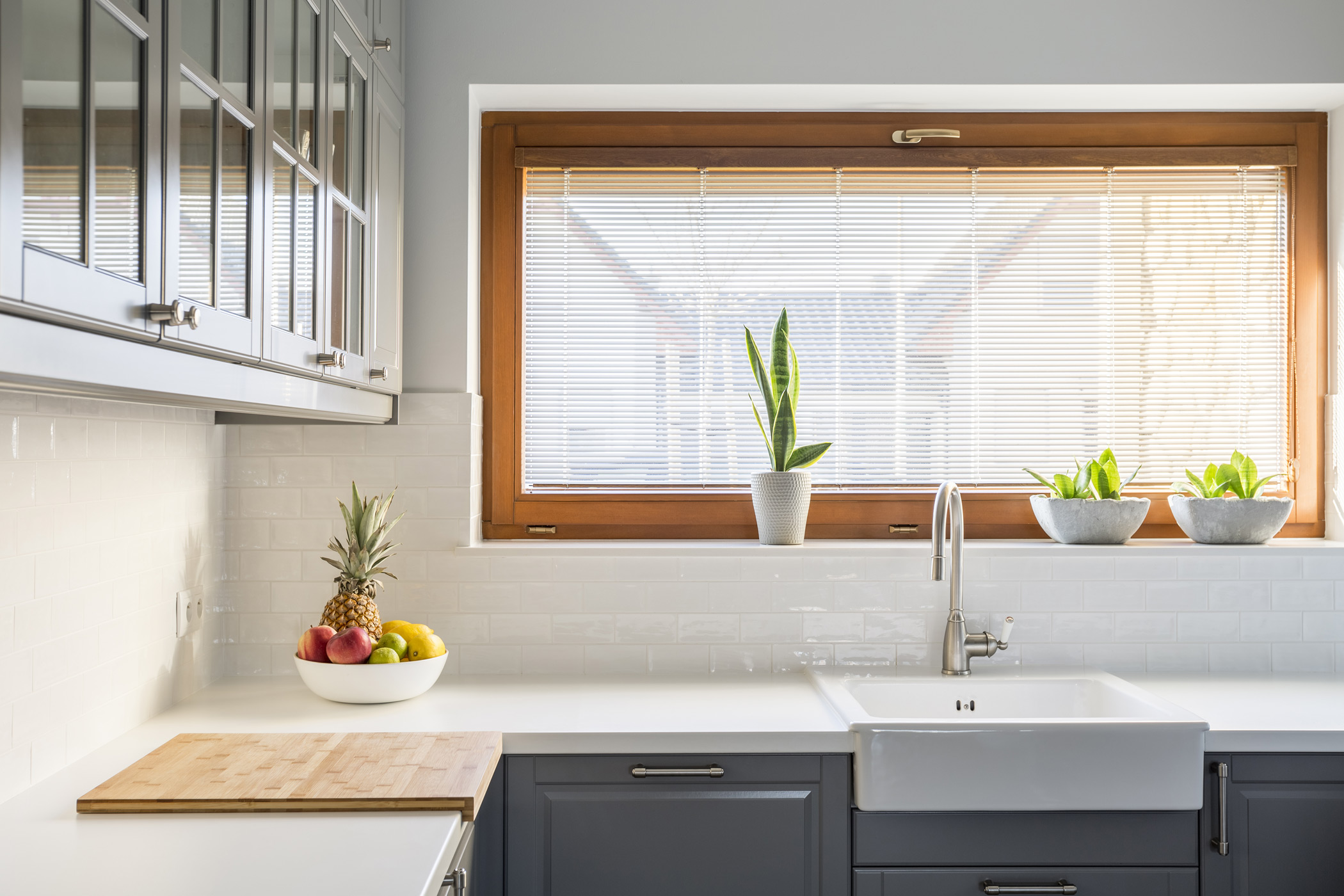 a bright kitchen sink and cabinets under an open window covered with open blinds